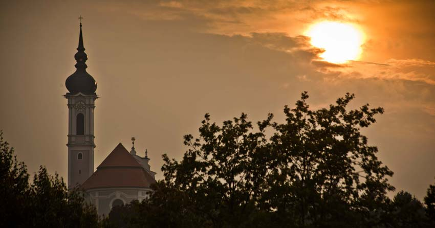 Watching the sun set over the silhouette of a church in Diessen.